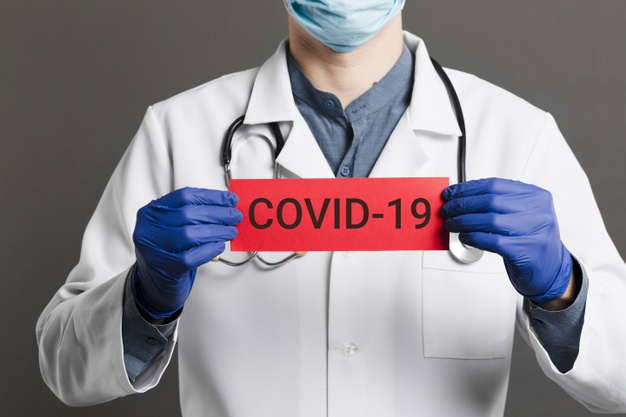 doctor-holding-covid-19-card_23-2148445988